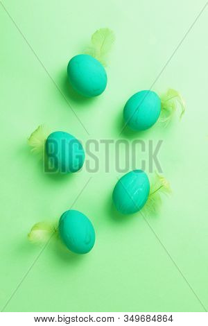 Colored Easter Eggs With Feathers On A Green Background. Monochrome. Top View.