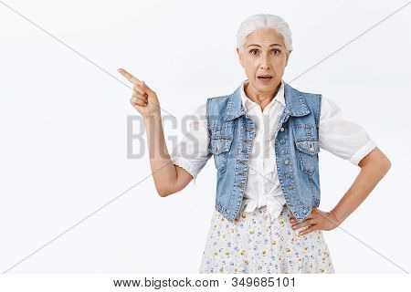 Intrigued, Unsure Pretty Senior Woman With Grey Combed Hair, Wear Vest And Dress, Pointing Fingers L