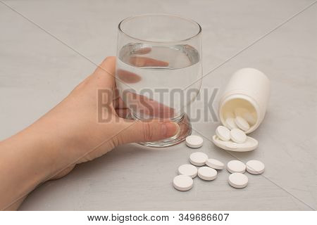 Woman Holds A Glass Of Water, Pills Are Scattered On A Gray Table.