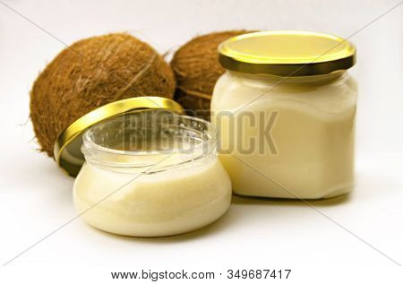Solid Homemade Coconut Oil In Glass Jar With Metal Gold Lid And Fresh Coconuts On White Background C