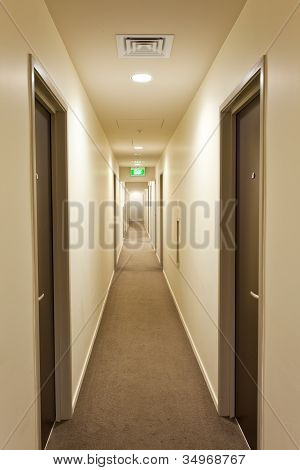 Long corridor with hotel room doors and exit sign