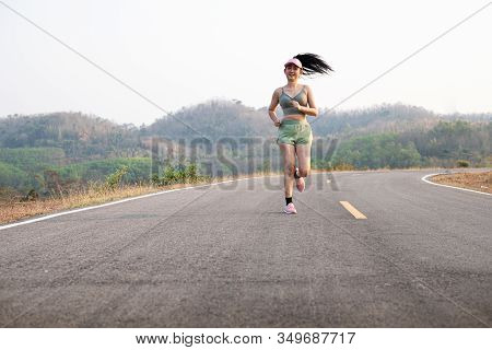 Photo Fone View Asia Young Smiling Woman Runner Running On Asphalt Road, Female In Sport Cloth And W