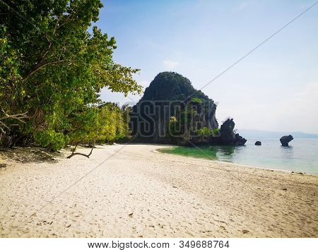 Exotic Island Beach Surrounded By Clear Blue Water And Limestone Rocks With Long Tail Boats. Empty I