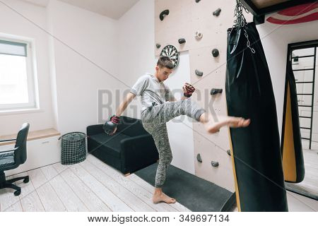 16-17 years old teenage boy workout with boxing bag in home gym room. Young teen male having hobby to be strong and sportish man.