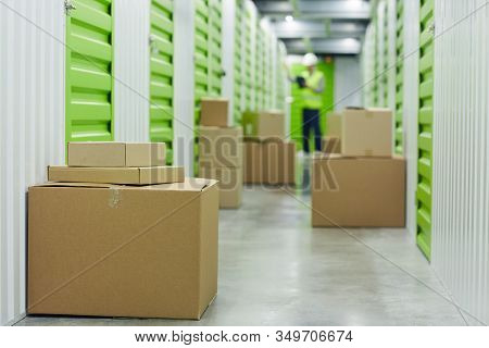 Close-up Of Cardboard Boxes Standing Near The Stockrooms With Manual Worker Working In The Backgroun