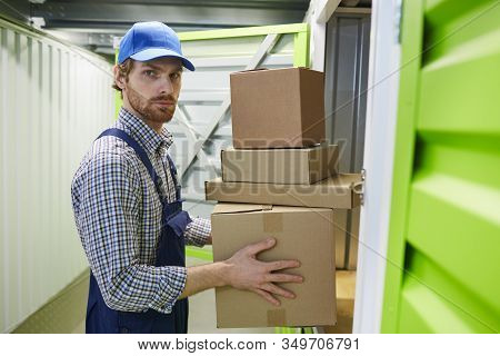 Portrait Of Young Man Looking At Camera While Putting The Heap Of Cardboard Boxes Into The Stockroom