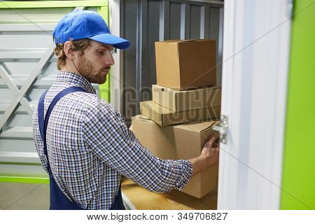 Young Worker In Cap And In Overalls Loading Cardboard Boxes Into The Stockroom And Shipping Them