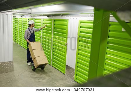 Young Man In Overalls Standing With Cart Of Load And Opening The Door Of Stockroom