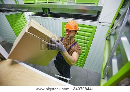 Man In Overalls And In Work Helmet Lifting The Load Into The Boxes While Working In Stockroom