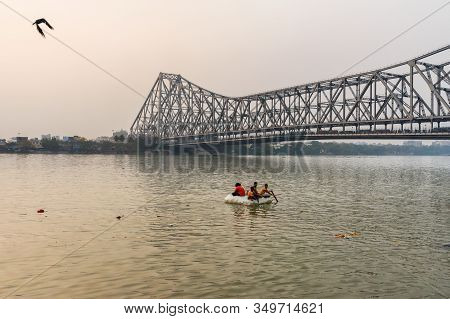 Kolkata, India - March 11, 2019: Indian Children Sail On Homemade Raft On Hooghly Or Ganga In Sunset