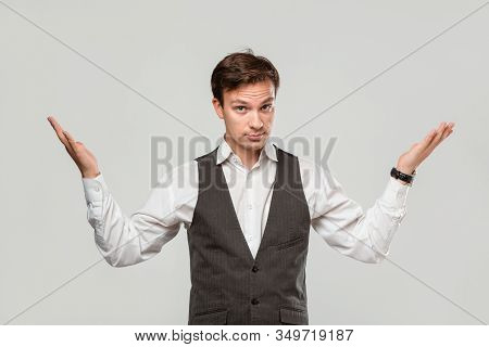 Young Businessman In A White Shirt And Grey Vest Shrugging His Shoulders Expressing Emotion Of Confu