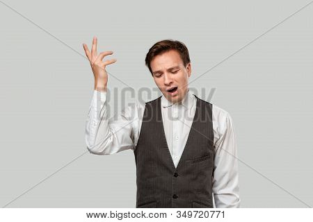 Young Businessman In A White Shirt And Grey Vest Expressing Gesture That He Does Not Know Answer. He