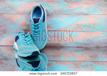 Blue Sport Shoes. Female Sneakers On Wooden Grungy Background With Copy Space. Sport Shoes On Blue B