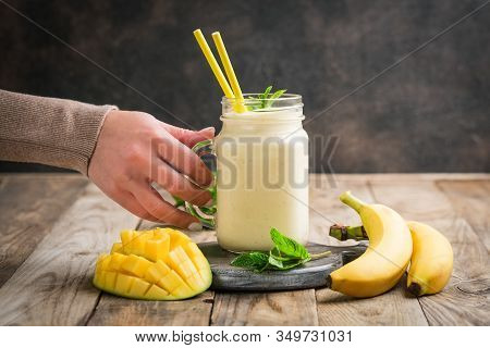 Female Hands With Mango And Banana Smoothie On A Rustic Background. Healthy Food, Detox Diet.