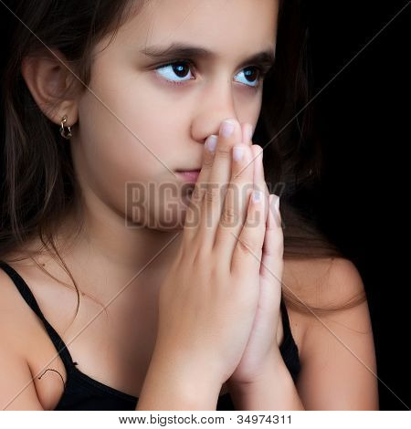 Close-up portrait of an hispanic girl praying isolated on black