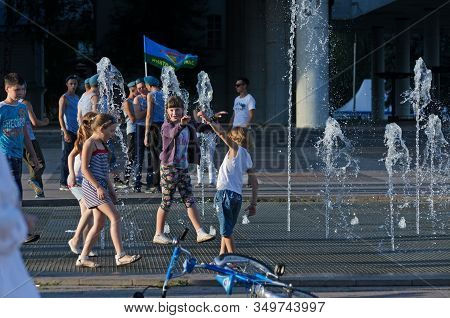 Children Play Near The Fountain On The Background Of Demobilized Paratroopers, During The Holiday Of