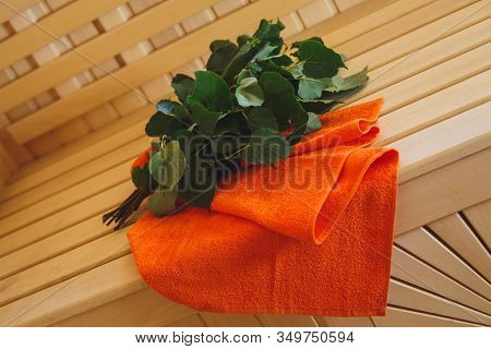 Bath Broom And Towel In A Sauna. Wooden Finishing Of The Room
