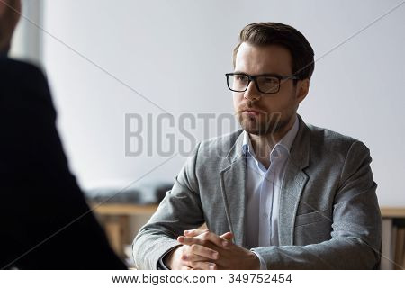 Serious Businessman With Clasped Hands Looking At Opponent At Negotiations