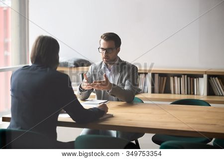 Two Businessmen Having Conversation, Sitting At Table In Boardroom