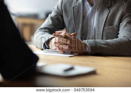 Two Businessmen With Clasped Hands Sitting Opposite Close Up