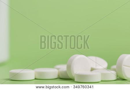 White Round Medicine Pills. Green Homogeneous Background. At The Top Of The Photo Place For A Banner