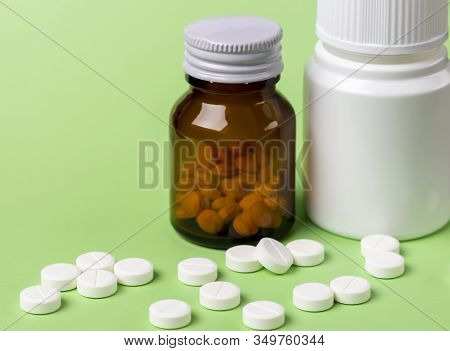 Two Glass Bottles Of Pills. Scattered White Round Tablets Next To Each Other. Green Flat Background.