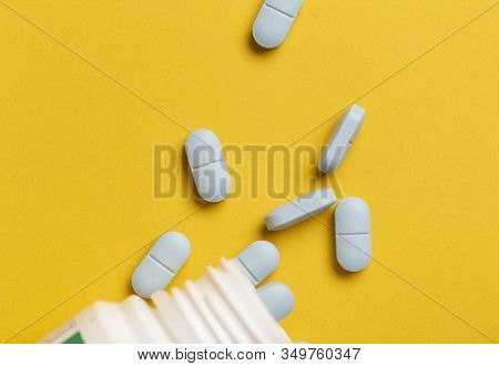 Medicine Bottle And Blue Pills Scattered Around On Yellow Background