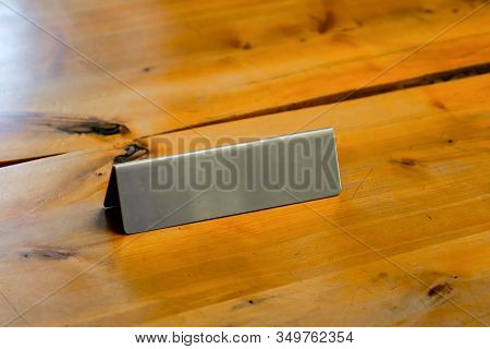 Blank Metallic Table Top Desk Identification Nameplate On A Wooden Desk