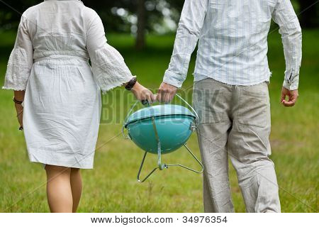 Back view of a couple in casual wear walking with a portable barbeque on an outdoor picnic
