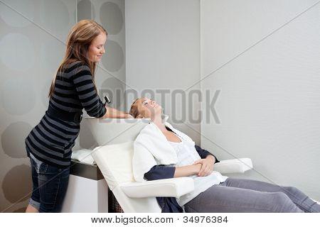Female beautician washing hair of her customer before haircut at beauty salon