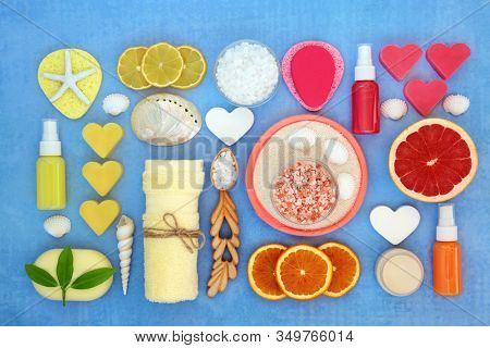 Beauty treatment for skincare with lemon and orange citrus fruit with spa, moisturising, exfoliation and cleansing products. Flat lay, top view, on blue background.