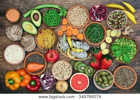 Health food for a healthy diet with foods and herbs high in antioxidants, anthocyanins, vitamins, minerals, protein, smart carbs, omega 3 and fiber. Flat lay on rustic wood.