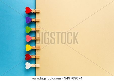 Small Decorative Clothespins In The Form Of Hearts Of Different Colors On A Blue And Yellow Backgrou