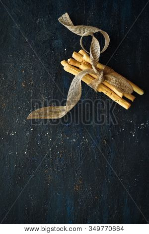Breadsticks Tied Together With A Ribbon On Dark Background, Breadsticks Side Layout, Italian Breadst