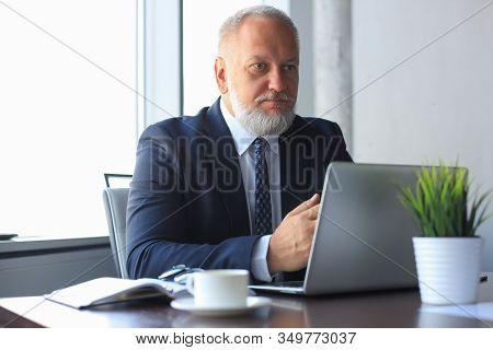 Senior Man In Office Working On Laptop Computer In Modern Office.