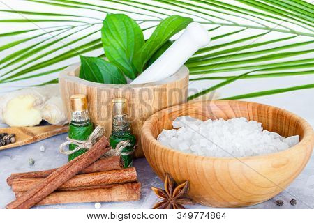 Closeup Wooden Bowl With Salt, Mortar Pounder With Herbs, Small Bottles With Aromatic Oils, Healing
