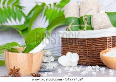 Closeup Wooden Mortar Pounder With Herbs On Table. Basket With Towel Rolls, Massage Stones, Bowl Wit