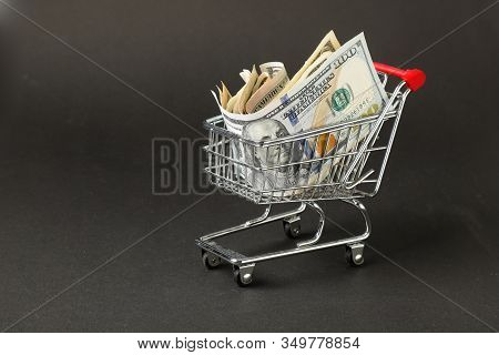 One Miniature Supermarket Shopping Cart Filled With Us Dollar Banknotes On A Dark Background.