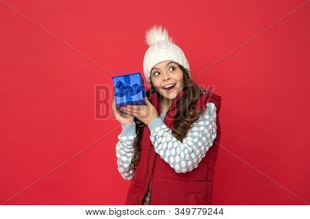 Xmas Gift Idea. Winter Holidays. Happy Kid In Winter Outfit Hold Gift Box Red Background. Wish List.
