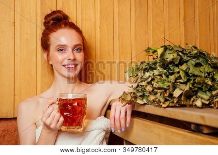Redhaired Ginger Woman Steaming In The Bathhouse With Russian Bunch Broom Drinking Beers.she Enjoyin