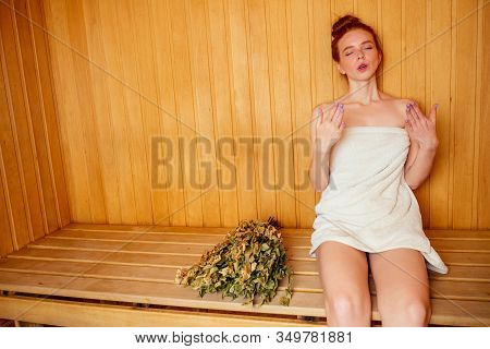 Redhaired Ginger Woman Steaming In The Bathhouse With Russian Bunch Birch Broom .she Enjoying Heat S