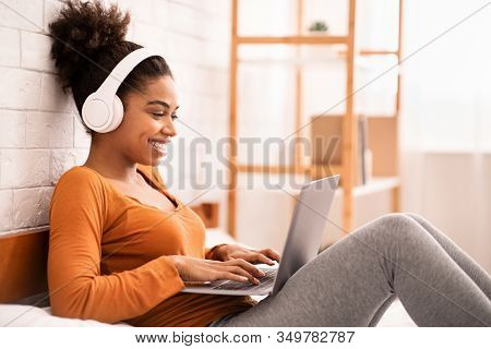 Smiling Afro Woman In Headphones Using Laptop Browsing Internet Relaxing Lying In Bed At Home. Weeke