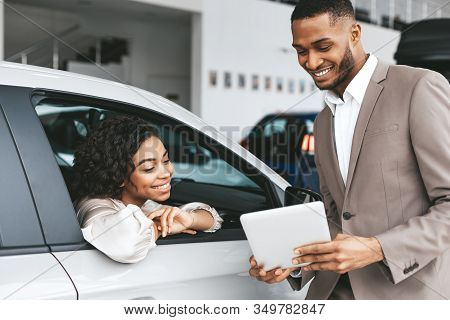 African American Woman Buying Car, Salesman Showing Papers And Documents Offering Deal In Auto Deale