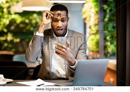 Shocking News. Shocked Afro Guy Touching Spectacles Using Smartphone, Surprised By Blocked Bank Acco