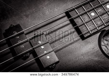 Bass Guitar With Four Strings In Black And White Closeup. Detail Of Popular Rock Musical Instrument.