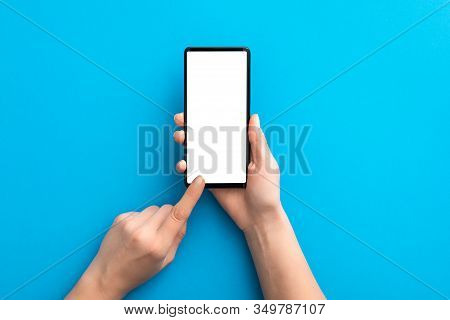 Hand Holding Black Phone Isolated On Blue Background And Clipping Path Inside. Smartphone Mock Up Co