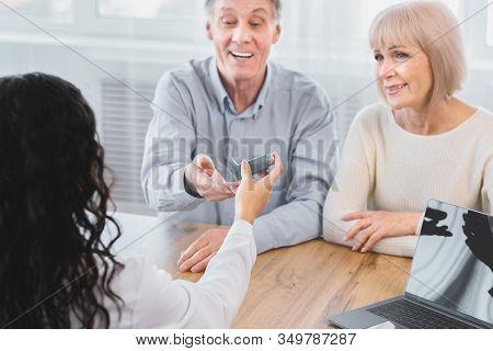 Asthma Treatment. Female Physician Giving Asthma Inhaler To Smiling Elderly Man, Senior Couple Sitti