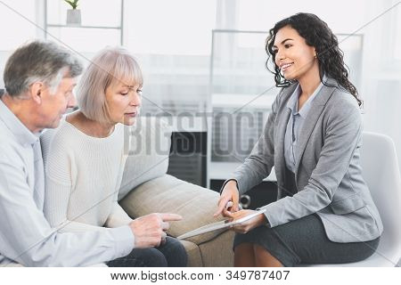 Latin Real Estate Agent Showing House Plans On Electronic Digital Tablet, Senior Couple Looking At A