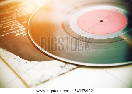 A Vintage Musical Black Vinyl Record Lies On The Paper Cover Of A Music Album, Illuminated By Sunlig