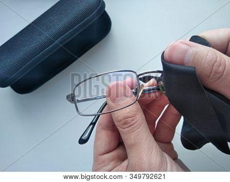 Black Modern Eyeglasses With Case.man Wipes With A Cloth The Glass From Contaminants.cleaning Glasse